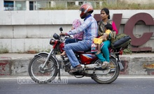 A man exposes the members of his family to risk by riding a motorcycle with his wife and two kids, who are without helmets, in a gross violation of law in capital's New Airport Road. Photo: asaduzzaman pramanik/ bdnews24.com