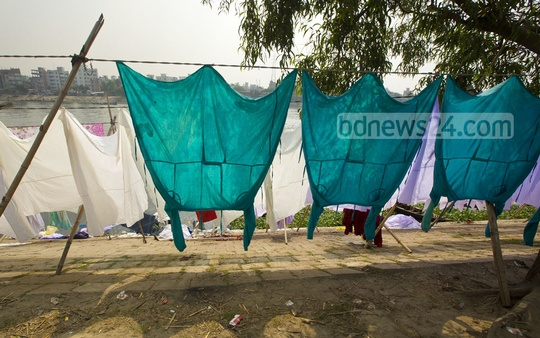 Clothes, including doctors' aprons and bed sheets, left to dry on Buriganga's bank after washed in its filthy water. The picture was taken from Kamrangir Char in Dhaka. Photo: mustafizmamun/bdnews24.com