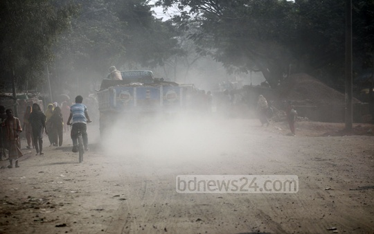 A cloud of dust blocks visibility every time a vehicle passes through the road linking Gabtoli to Mohammadpur. Photo: nayan kumar/ bdnews24.com