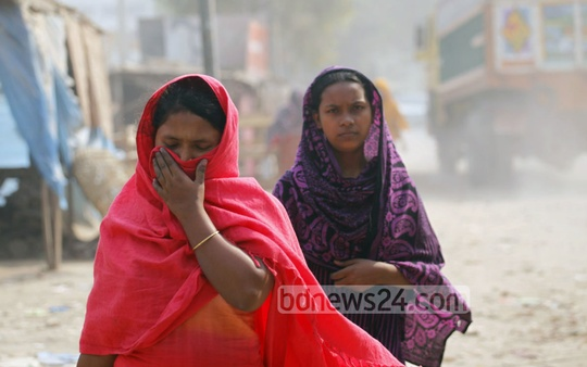 People need to cover their noses to avert dust while walking on the road linking Gabtoli to Mohammadpur. Photo: nayan kumar/ bdnews24.com