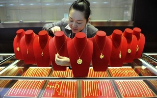A shop assistant arranges gold accessories at a gold store in Lin'an, Zhejiang province Nov 6, 2014. Reuters