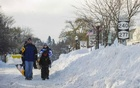 People carrying shovels walk in the street beside tall snowbanks in Buffalo, New York, November 21, 2014. Credit: Reuters