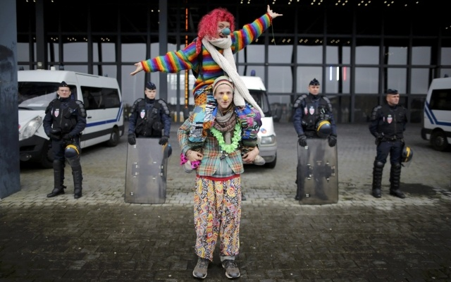 French riot police stand guard as people dressed as clowns attend a protest demonstration against