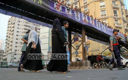 Police stop three women as they try to cross the street violating traffic law at Banglamotor in Dhaka on Tuesday. Photo: asif mahmud ove/ bdnews24.com