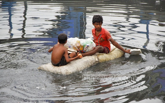 Children are collecting empty plastic bottles floating on Buriganga River by making a makeshift raft of sacks. Photo: nayan kumar/ bdnews24.com