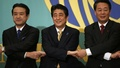 Japan's Prime Minister and leader of the ruling Liberal Democratic Party (LDP) Shinzo Abe (C) poses holding hands with Democratic Party of Japan leader Banri Kaieda (R) and Japan Innovation Party co-leader Kenji Eda before a debate session with seven other party leaders ahead of the December 14 lower house election in Tokyo December 1, 2014. REUTERS/