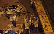 Workers clean a main road as protest banners are displayed on top of a bus stop outside the government headquarters in Hong Kong, December 11, 2014. REUTERS