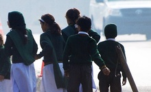 Schoolchildren cross a road as they move away from a military run school that is under attack by Taliban gunmen in Peshawar, Dec 16, 2014. Reuters