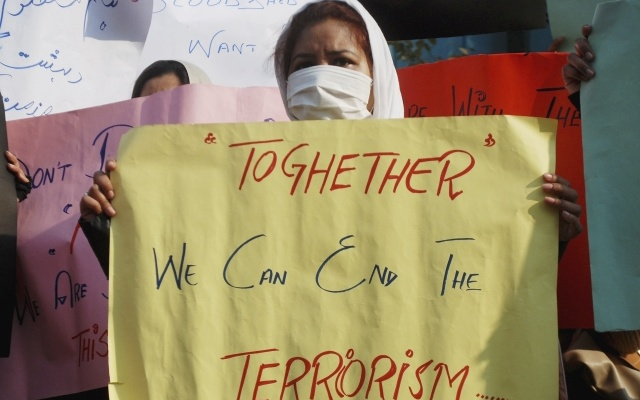A woman holds a placard during a protest to condemn the Taliban attack on the Army Public School, during a rally in Peshawar, December 17, 2014. REUTERS