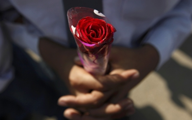 A student, holding a rose, takes part in a prayer for victims of the Taliban attack on the Army Public School in Peshawar, in Karachi, December 17, 2014. REUTERS