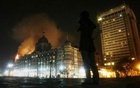 A reporter talks on her phone as smoke is seen coming from Taj Hotel in Mumbai, November 27, 2008. Reuters