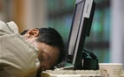 A man sleeps after monitoring stock market prices on computer monitors inside a securities company in Taipei Jan 15, 2009. Reuters