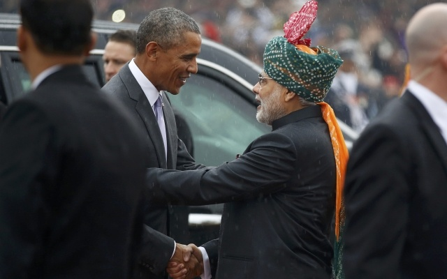 US President Barack Obama (L) shakes hands with India's Prime Minister Narendra Modi in the pouring rain as he arrives to attend the Republic Day parade in New Delhi January 26, 2015. REUTERS/