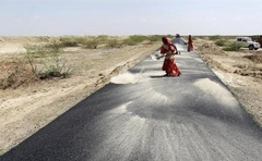 Women labourers throw dust on a road tarmac under construction at Bharadva village in Gujarat April 23, 2013. Reuters