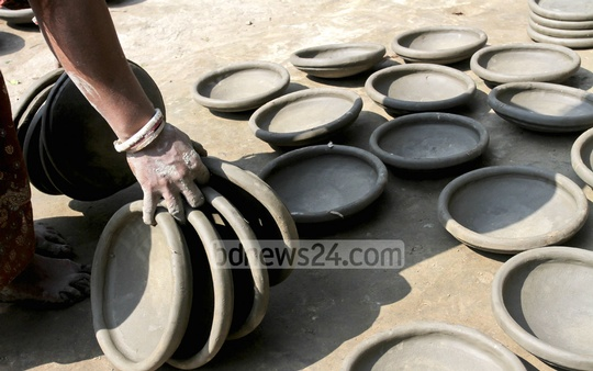 A woman drying earthen pots. The photo was taken recently at Munshiganj's Srinagar. Photo: tanvir ahammed/ bdnews24.com
