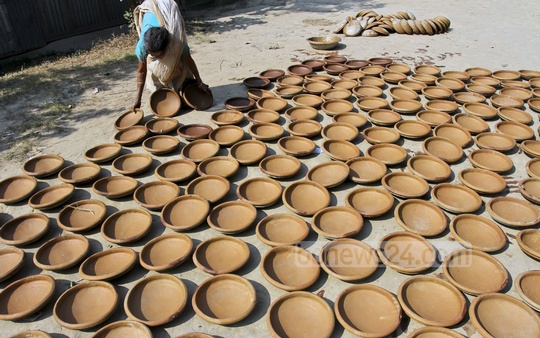 A women colouring a pottery product. Photo was taken from Munshiganj's Sirajdikhan Upazila. Photo: tanvir ahammed/ bdnews24.com