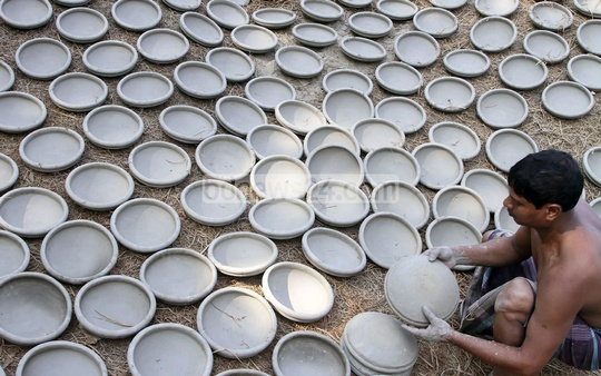 A man drying earthen pots. The photo was taken recently at Munshiganj's Srinagar. Photo: tanvir ahammed/ bdnews24.com