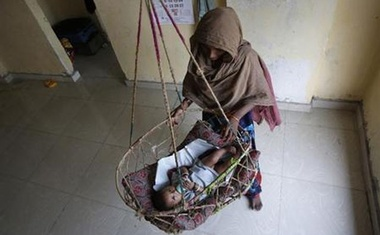 A woman tends to a baby sleeping in a hanging cot in the living room on the outskirts of Mumbai April 10, 2013. Reuters
