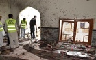 Rescue workers and a policeman stand at the site of an explosion in a Shi'ite mosque in Shikarpur, in Pakistan's Sindh province Jan 30, 2015. Reuters