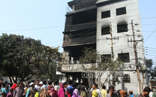 Curious bystanders look at a multi-storey factory that caught fire on Saturday, killing at least 12 people. Photo: nayan kumar/ bdnews24.com