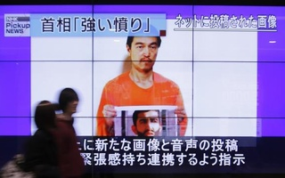 People walk past television screens displaying a news program, about an Islamic State video showing Japanese captive Kenji Goto, on a street in Tokyo Jan 28, 2015. Reuters
