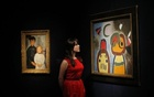 A member of staff poses with ''L'oiseau au plumage deploye vole vers l'arbre argentee'' (R) by Joan Miro at Christie's auction house in London, January 30, 2015. Reuters