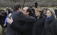 France's President Francois Hollande (C) embraces Spain's Prime Minister Mariano Rajoy as German Chancellor Angela Merkel (2nd R) look on while they walk on a field near the crash site of Germanwings Airbus A320 near Seyne-les-Alpes March 25, 2015. Reuters