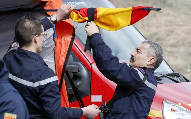 French firefighters install a black ribbon on a German flag outside a tent where relatives and officials are due to pay tribute to the victims of the Airbus A320 crash, outside Le Vernet near Seyne-les-Alpes, March 25, 2015. Reuters