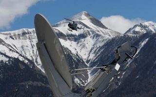 A rescue helicopter from the French Gendarmerie lands behind a media satellite dish seen during operations near the crash site of an Airbus A320, in Seyne-les-Alpes, March 26, 2015. Reuters