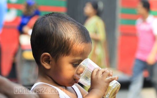 A child drinks beverage, bought from a footpath vendor at Dhaka's Farmgate, to get relief from scorching heat on Friday. Photo: asif mahmud ove/ bdnews24.com