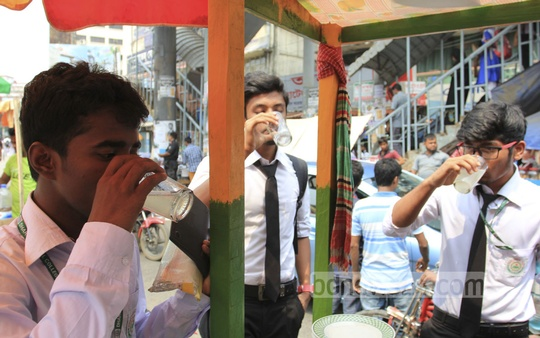People drinking beverage bought from a footpath vendor at Farmgate in Dhaka to beat scorching heat on Friday. Photo: asif mahmud ove/ bdnews24.com