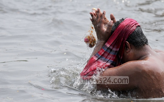 A devote take 'Ashtami Snan', the Hindu ritual of holy bath in the Old Brahmaputra River at Langalbandh, Narayanganj, on Friday. Photo: tanvir ahammed/ bdnews24.com
