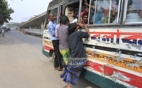 People commute in buses risking their lives. This photo was clicked in Dhaka on Monday. Photo: asif mahmud ove/ bdnews24.com
