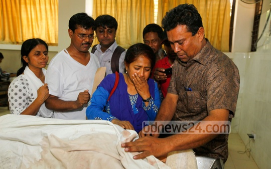 Relatives of 45-year-old Pinky Biswas, who was killed in an unusual attack by an associate, mourn near her body at Dhaka Medical College and Hospital on Tuesday. Photo: bdnews24.com