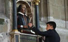 Christian Van Nieuwerburgh places a symbolic quill in the hand of a statue of William Shakespeare, marking the 450th anniversary of his birth inside Holy Trinity Church in Stratford-upon-Avon, in this April 26, 2014 Reuters file photo.