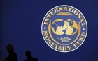 Visitors are silhouetted against the logo of the International Monetary Fund at the main venue for the IMF and World Bank annual meeting in Tokyo October 10, 2012. Reuters