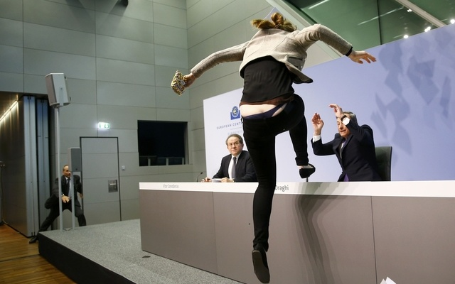 A protester jumps on the table in front of the European Central Bank President Mario Draghi during a news conference in Frankfurt, April 15, 2015. REUTERS