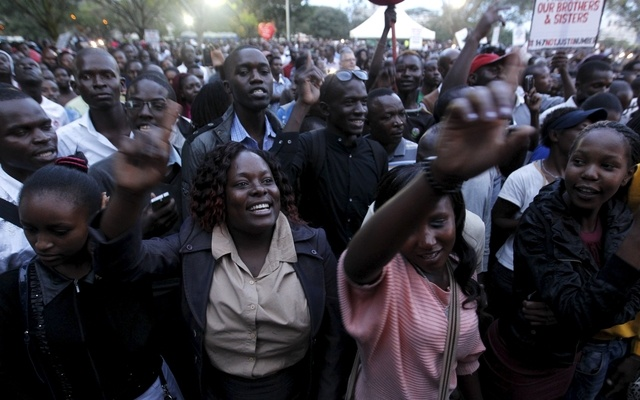 People gesture as they attend a memorial concert for the Garissa university students who were killed during an attack by gunmen, at the