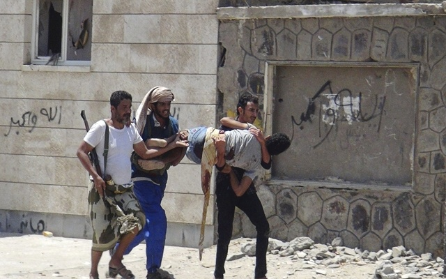ATTENTION EDITORS - VISUAL COVERAGE OF SCENES OF INJURY OR DEATH Fighters loyal to Yemen's President Abd-Rabbu Mansour Hadi carry a comrade who was injured during clashes withHouthi fighters outside Hadi's house in the country's southern port city of Aden April 19, 2015. REUTERS