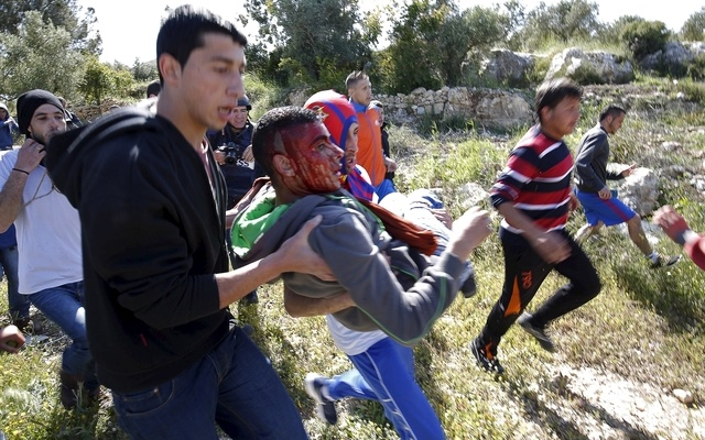 Palestinians evacuate a protester, whom witnesses said was shot and wounded by Israeli troops, during clashes following a protest against Jewish settlements in the West Bank village of Nabi Saleh, near Ramallah April 24, 2015. REUTERS
