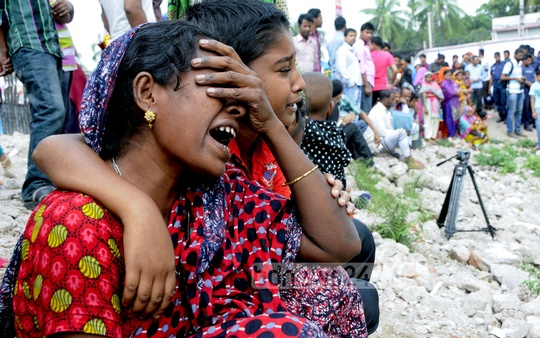 Relatives break down in tears in front of the site of collapsed Rana Plaza on the second anniversary of the disaster on Friday. Photo: bdnews24.com
