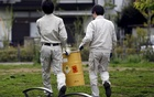 Workers of Tokyo's Toshima ward office carry away a container holding a fragment of an unknown object after it was dug up from the ground near playground equipment at a park in Toshima ward, Tokyo April 24, 2015. Reuters