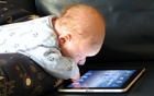 A baby uses iPad. Photo taken from playfulearlylearners.com