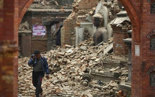 A man cries as he walks on the street while passing through a damaged statue of Buddha a day after an earthquake in Bhaktapur, Nepal Apr 26, 2015. Reuters
