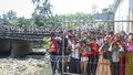 Local residents throng Darshan Deuri area in Sylhet as a missing schoolboy's body found in a sewer there on Monday.