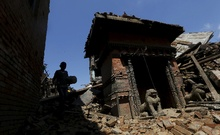 A boy carrying a bolster walks past a damaged temple after Saturday's earthquake in Bhaktapur, Nepal April 27. Reuters