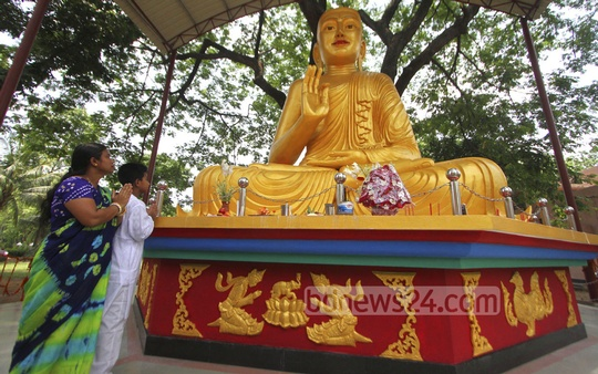 Buddhist devotees take part in prayers in Dhaka University's Jagannath Hall on Sunday to mark Buddha Purnima .