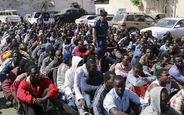 Migrants sit at a detention center after they were detained by the Libyan authorities in Tripoli, Libya May 17, 2015. REUTERS
