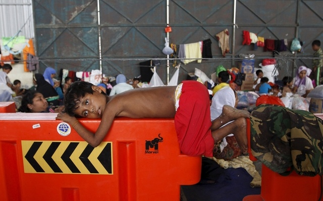 A Rohingya child, who recently arrived in Indonesia by boat, rests on a barrier at a shelter in Kuala Langsa, in Indonesia's Aceh Province, May 17, 2015. REUTERS