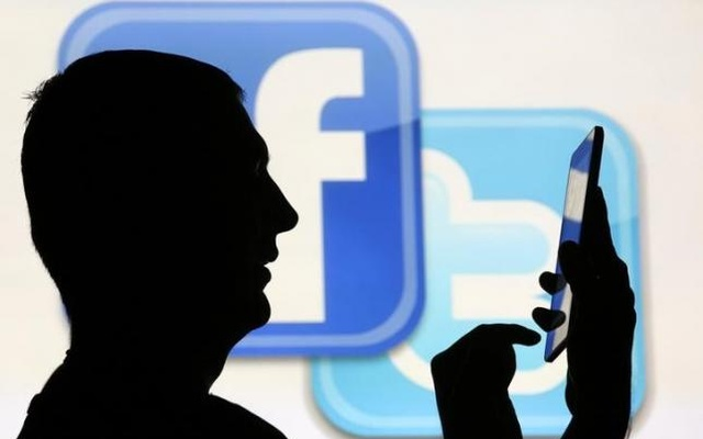 Representational Image: A man is silhouetted as he uses a mini tablet computer while standing in front of a video screen with the Facebook and Twitter logos, in this picture illustration taken in Sarajevo October22, 2013. Reuters
